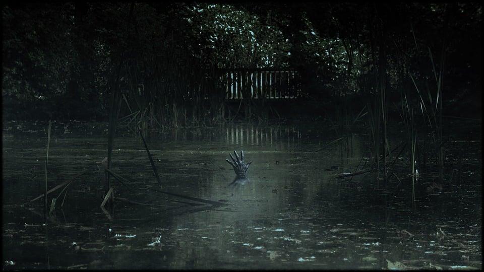 Mão humana emergindo de pântano.