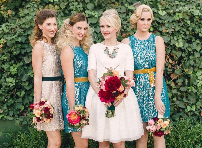 Quatro mulheres vestidas em estilo hipster. Duas estão usando vestidos na cor nude e as outras duas, vestidos no tom azul. Ao fundo parede com folhagem. Todas estão segurando um buquê de flores coloridas.