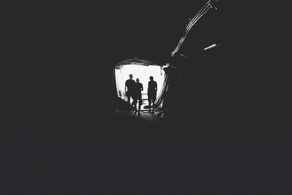 Três pessoas no fim de um túnel.
