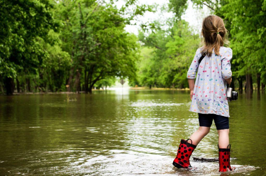 Criança menina com galochas caminha sobre enchente de rio.