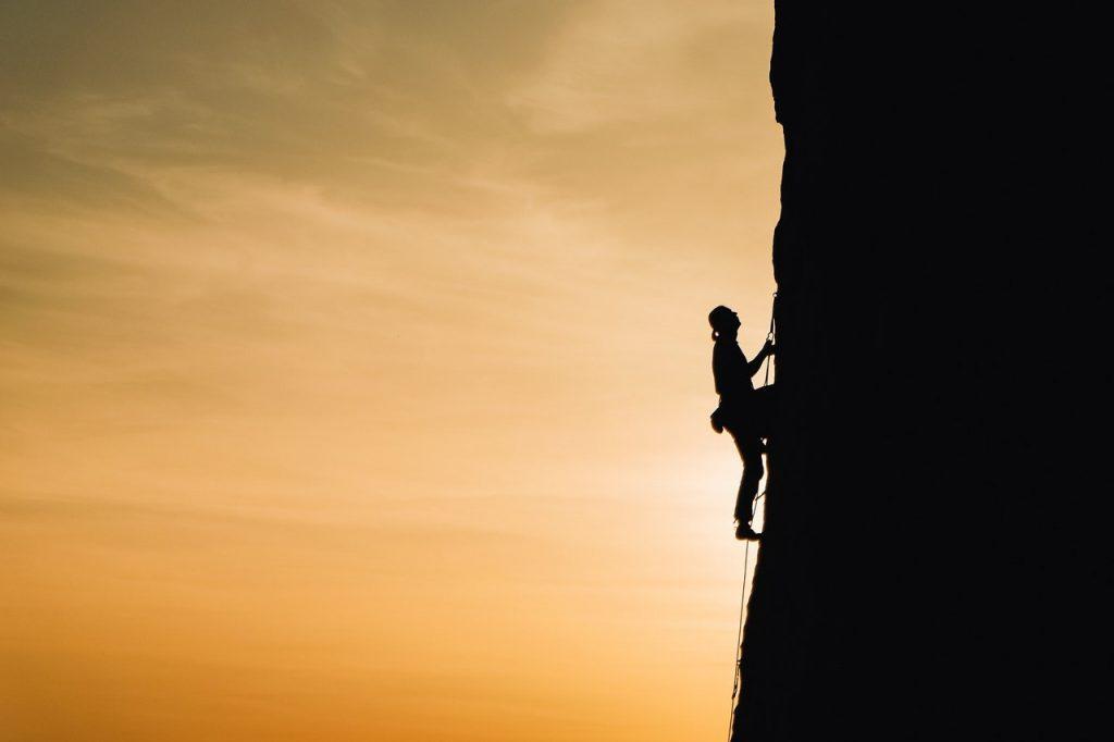 Mulher escalando uma montanha ao pôr do sol.