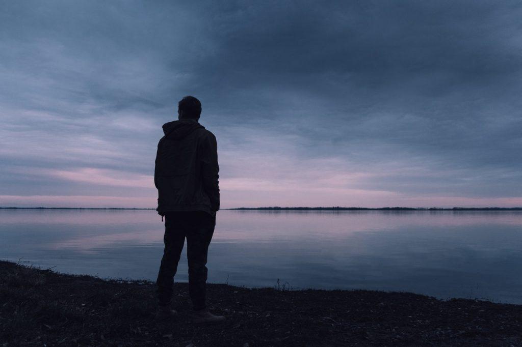 Homem em pé soziznho de costas em frente a um rio.