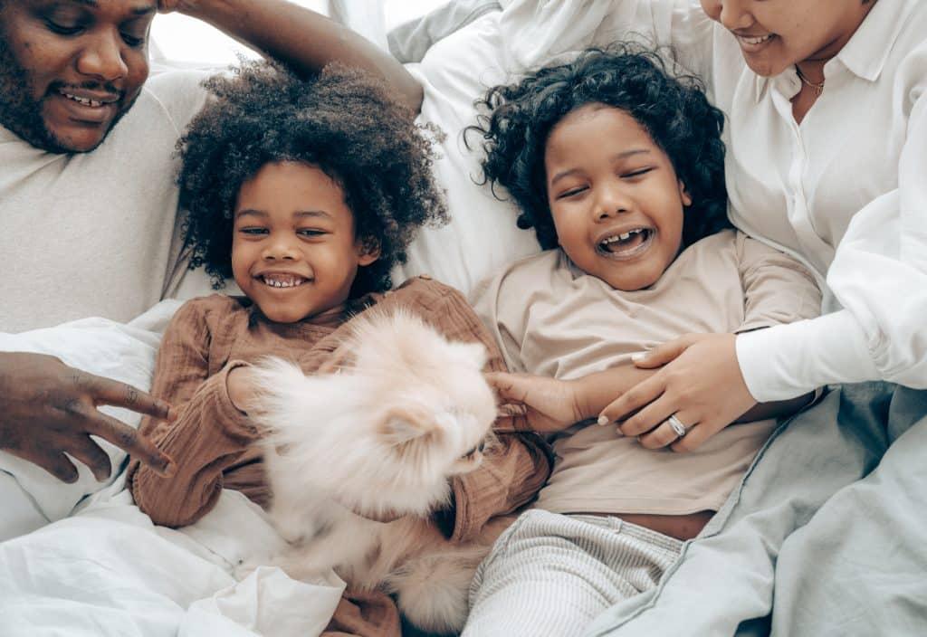 Crianças sorrindo ao lado de seus pais