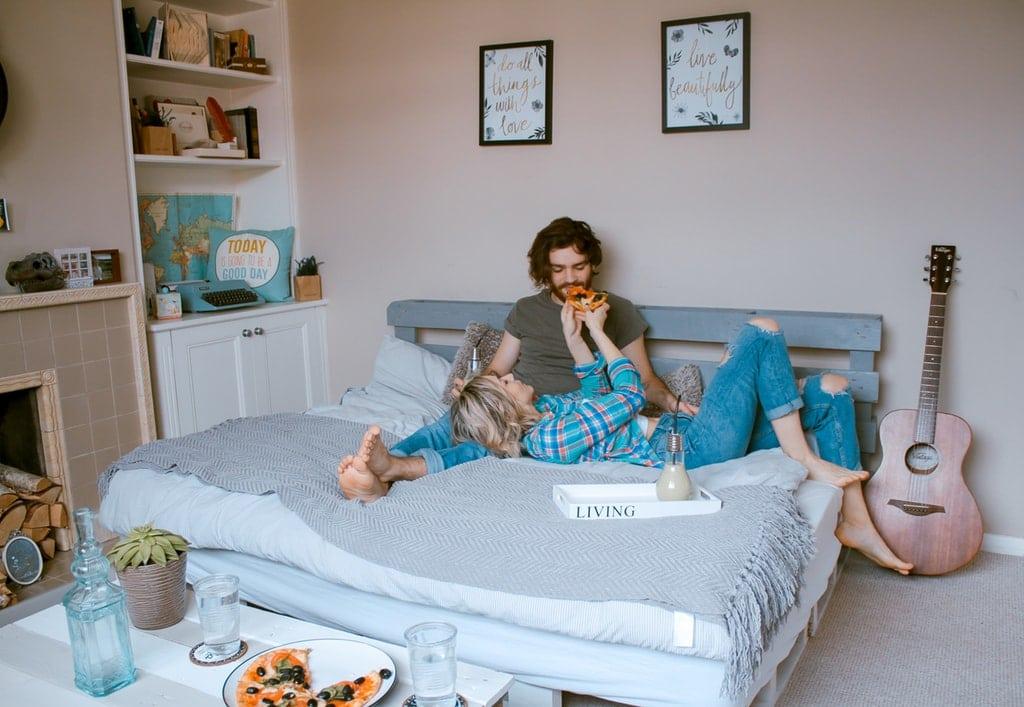 Casal jovem deitado em cama de casal comendo mamão e tomando leite.