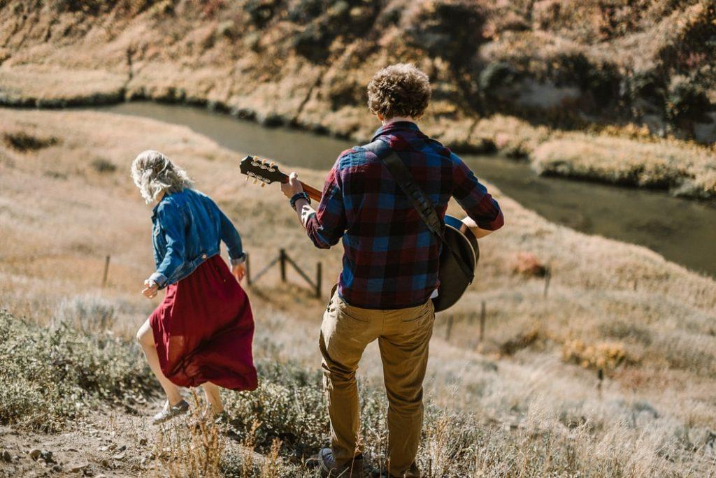 Mulher descendo montanha, e atras dela um homem toca violão.