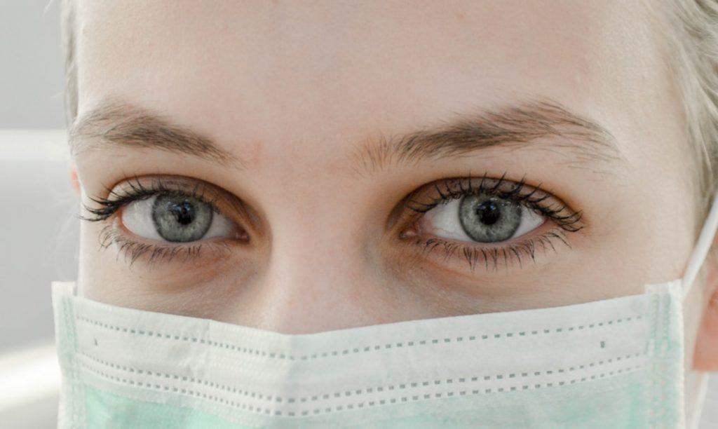 Mulher usando máscara de hospital, apenas seus olhos azuis estão expostos.