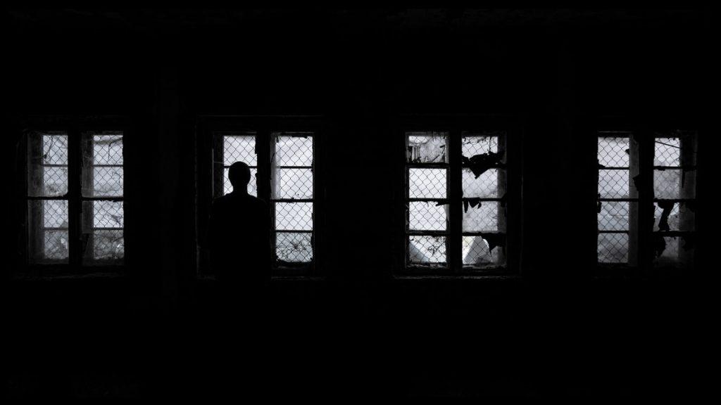 Silhueta de pessoa parada em frente a janela com tela de proteção.