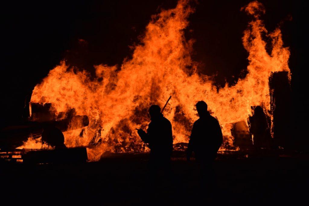 Silhueta de pessoas andando perto de incêndio.