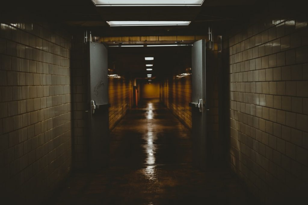 Corredor sombrio com portas de emergência abertas