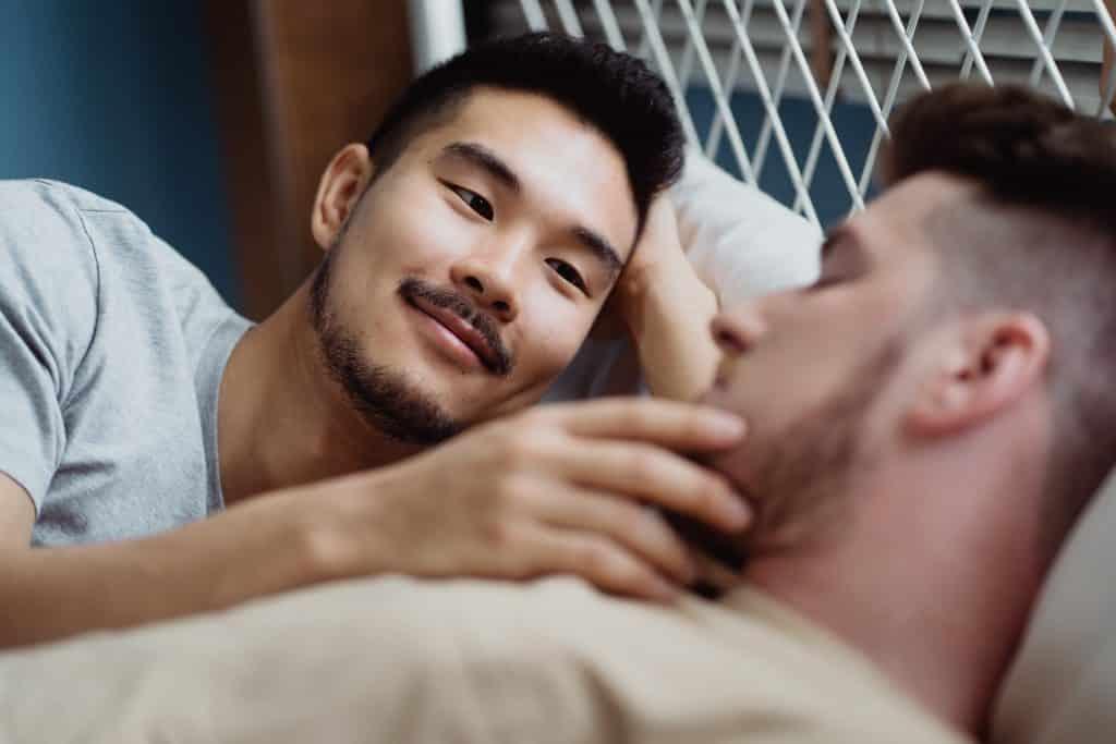 Dois homens deitados na cama, abraçados, enquanto um acaricia o rosto do outro.