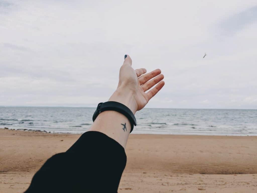 Mulher com a mão estendida em frente à praia.