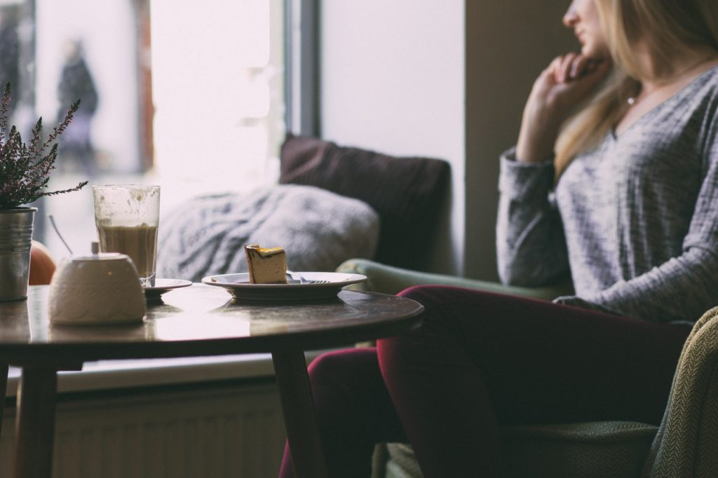 Mulher loira sentada ao lado de uma janela com expressão pensativa. Ao lado, uma mesa com um copo e um pedaço de torta.