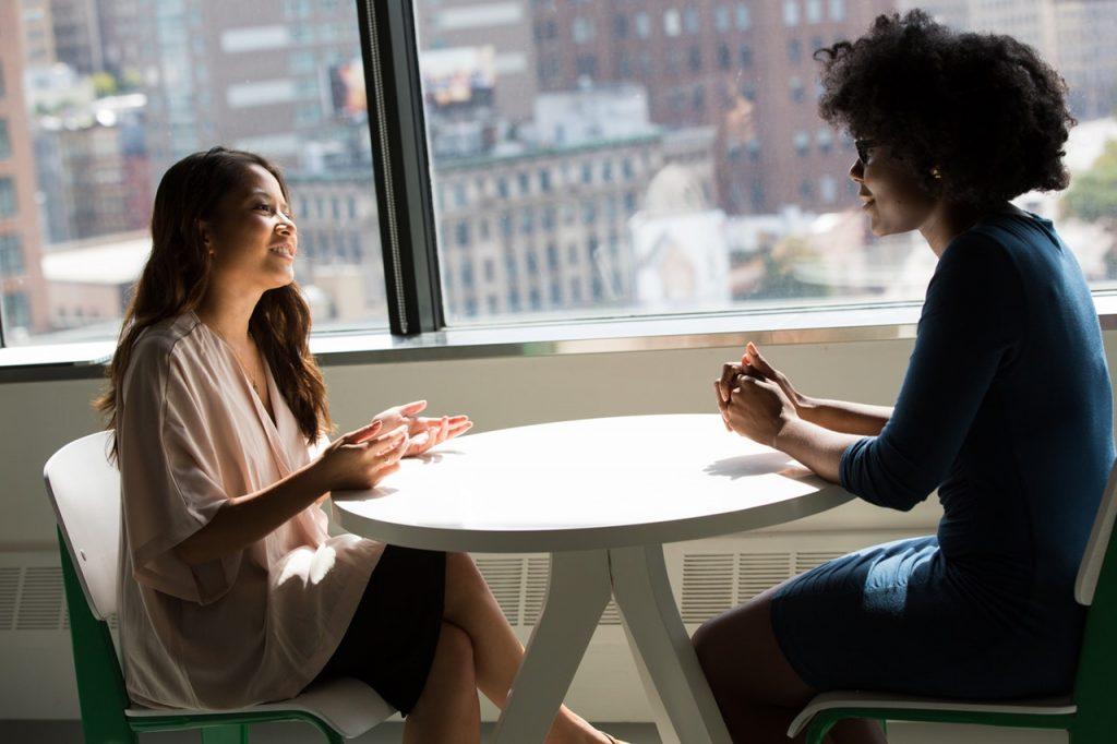 Duas mulheres sentadas em uma mesa conversando.