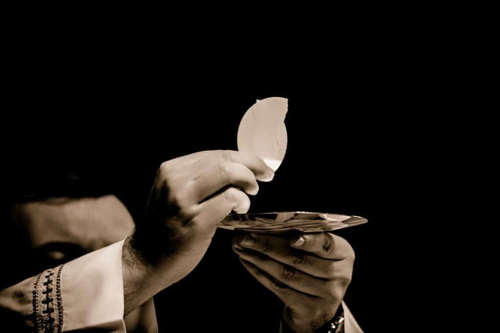 Mãos de um padre em preto e branco segurando uma hóstia.