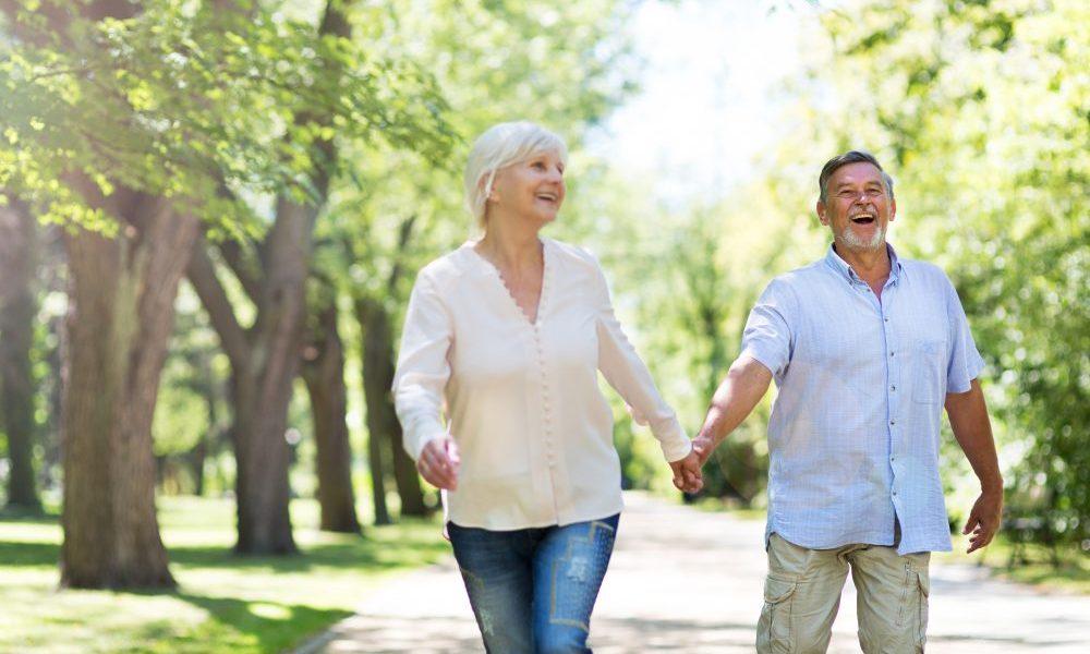 Casal de mãos dadas, caminhando em um parque cheio de árvores em um dia ensolarado. Ambos estão alegres e sorrindo.