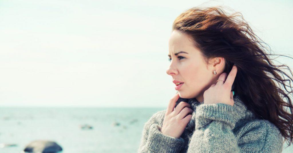 Imagem com o fundo do mar. Ao lado direito a imagem de uma mulher. Ela está olhando para o infinito, com seus cabelos ao vento. Ela veste uma blusa de lã na cor cinza claro.