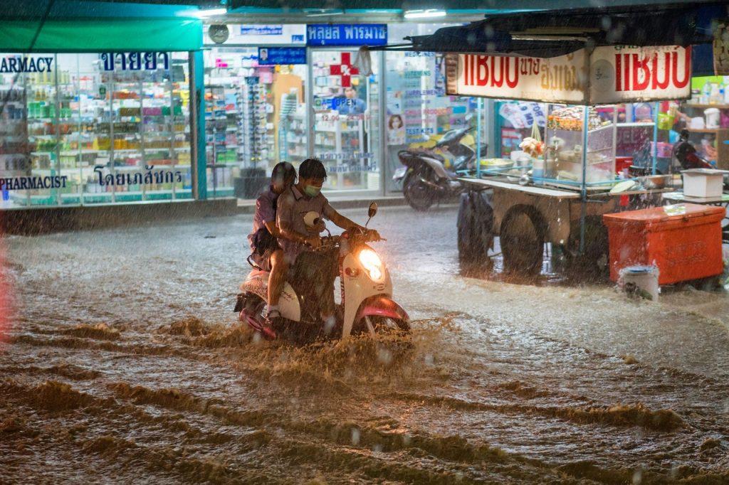 Motociclista tenta atravessar uma rua alagada sob chuva forte na cidade.