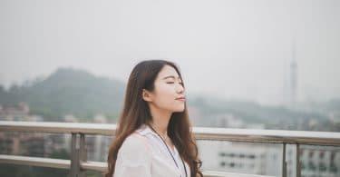 Mulher asiática de olhos fechados.