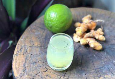 Copo com suco ao lado limão e gengibre sobre uma mesa de madeira.