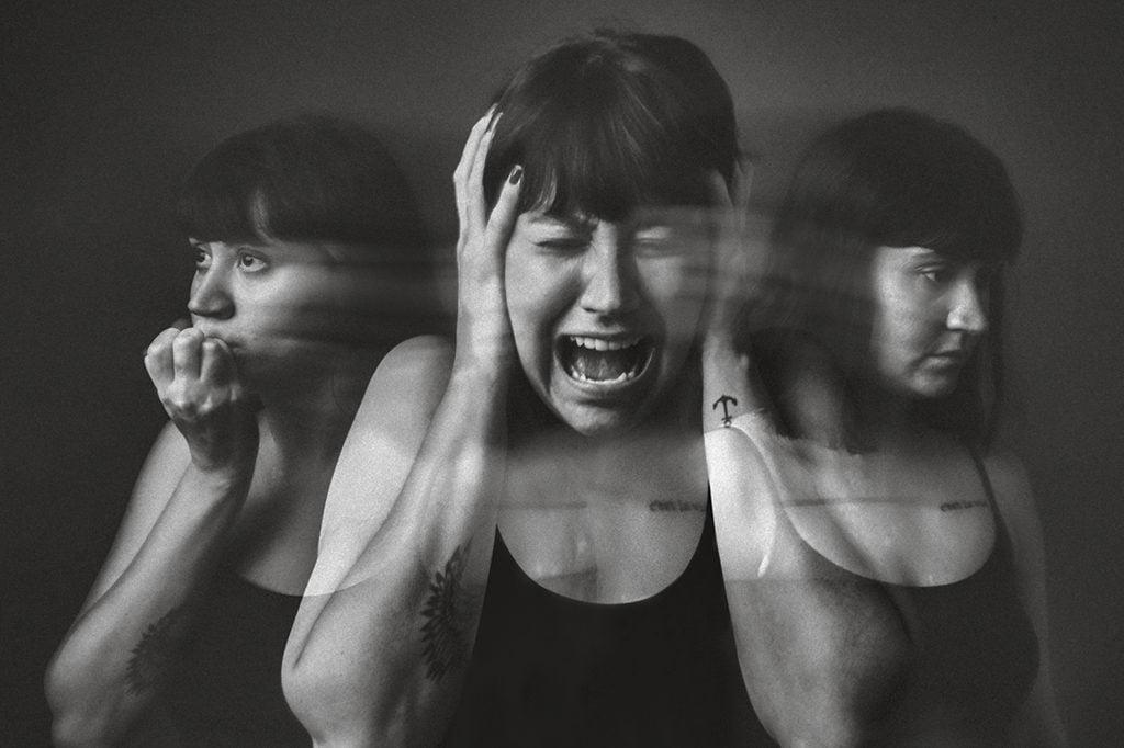 Imagem em preto e branco com uma  mulher com as mãos sobre os ouvidos e gritando. Ao lado dela temos suas sombras. Uma das sombras está com a mão na boca e a outra sombra pensativa.
