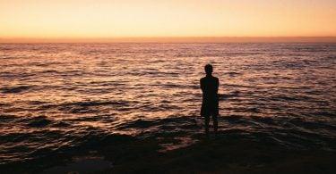 Silhueta de uma pessoa de frente para o mar durante o nascer do sol.