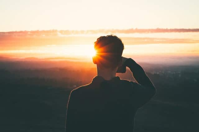 Garoto de costas com pôr-do-sol ao fundo