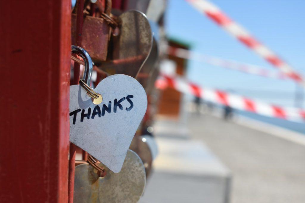 """Cadeado preso a uma grade com os dizeres """"obrigado"""" em inglês."""