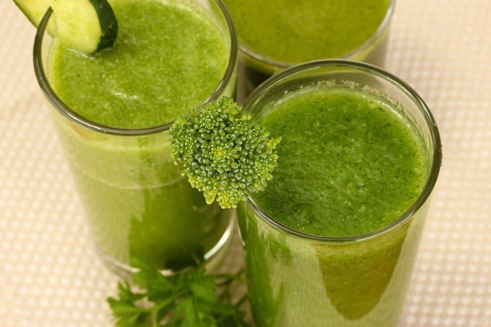 Três copos grandes contendo suco detox. Os copos estão decorados com pepino, brócolis e salsinha.