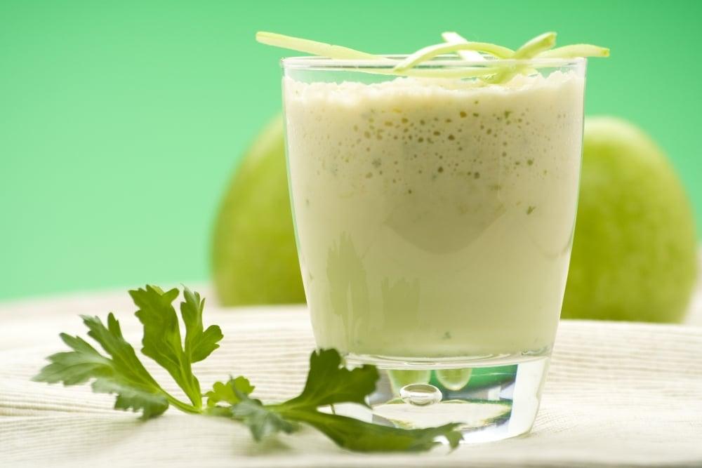 Copo com suco detox na cor verde. Ao fundo duas maças verdes e ao lado do copo um ramo de salsinha para decorar.