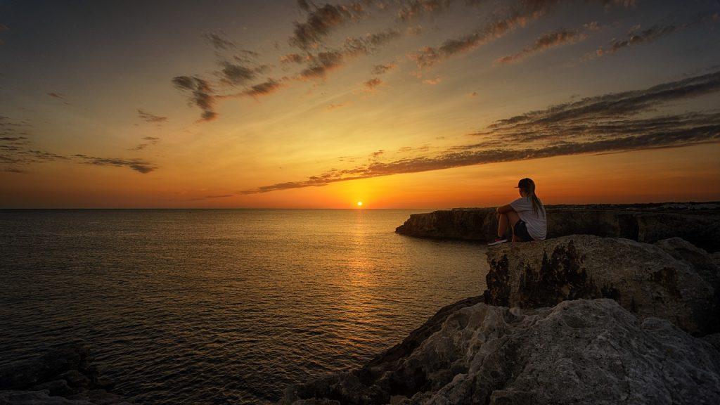 Imagem de um mar. Ao fundo o pôr do sol. Ao seu entorno várias pedras grandes. Em uma delas, encontra-se uma mulher sentada, olhando para o pôr do sol.