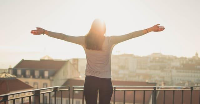 Mulher de costas com braços abertos com sol refletindo