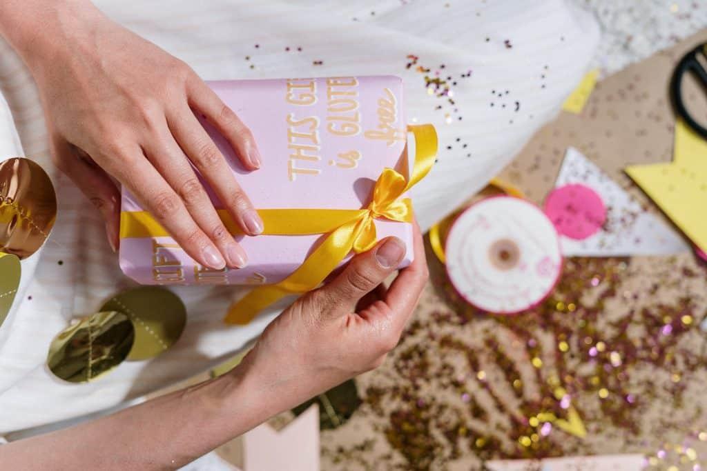 Mulher segurando uma caixinha lilás com um laço amarelo.