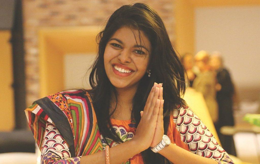 Mulher sorridente com as palmas das mãos encostadas em sinal de agradecimento.