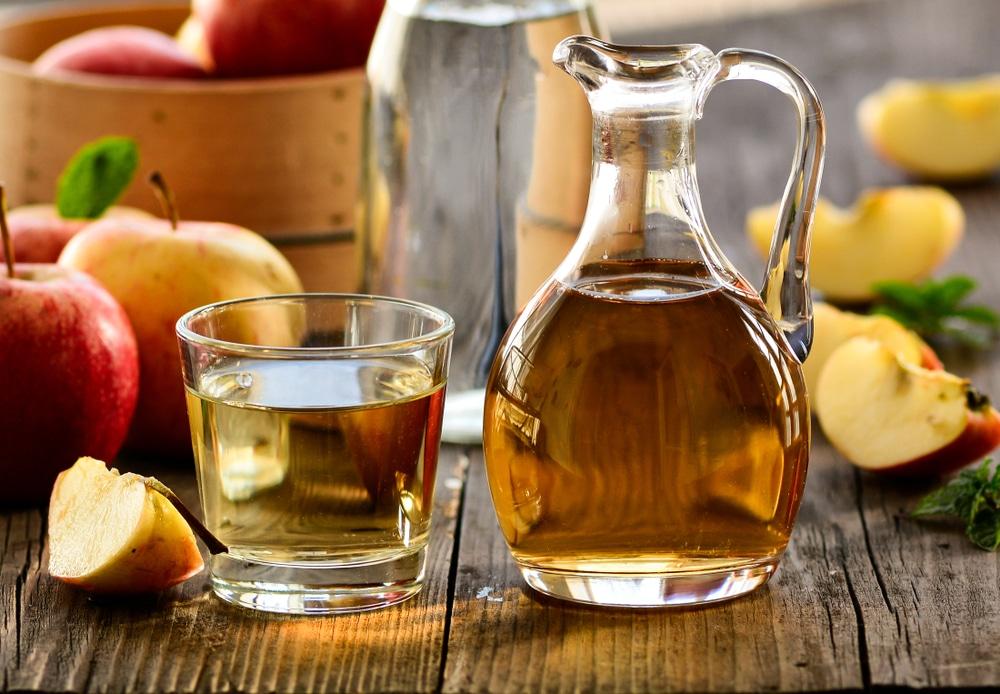 Uma jarra de vidro com vinagre de maçã. Ao lado dela um copo de vidro cheio de vinagre de maçã. Ambos estão dispostos sobre uma mesa de madeira com maças inteiras e cortadas ao meio.