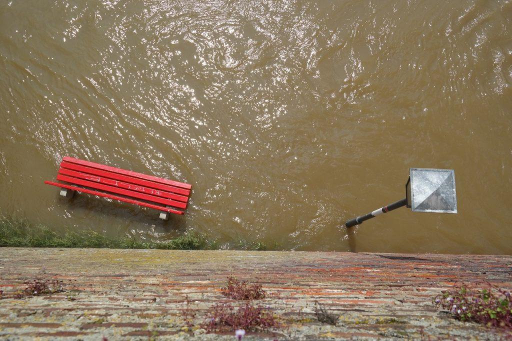 Rua alagada por água suja vista de cima, apenas com parte de um banco vermelho e um poste de luz à mostra.