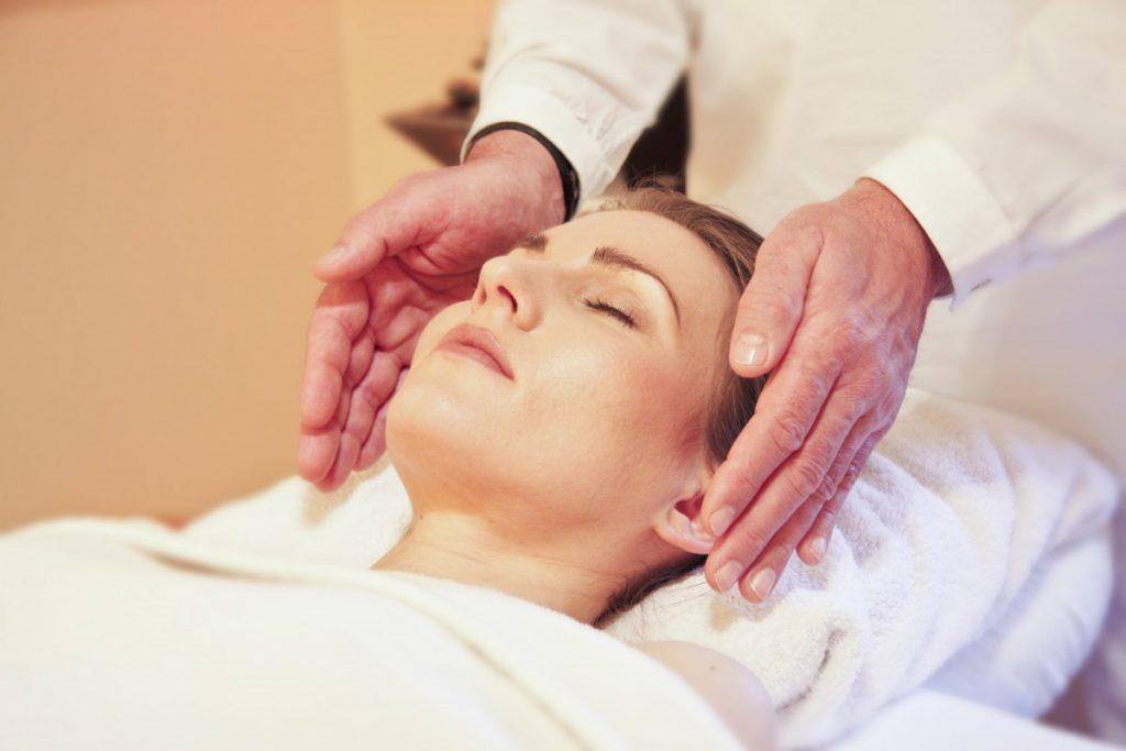 Mulher com olhos fechados recebendo tratamento de Reiki na cabeça. O terapeuta mantém as duas mãos nos lados da cabeça da mulher, porém sem encostar.