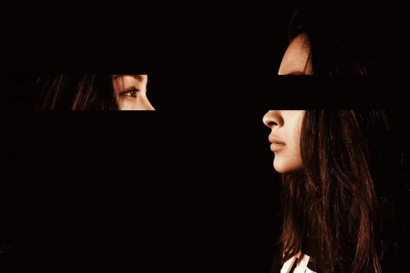 Mulher com os olhos recortados olhando para si mesma.