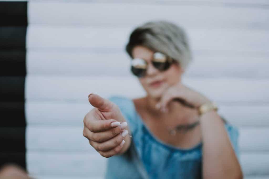 Mulher loira de óculos escuros estendendo a mão para prestar ajuda.