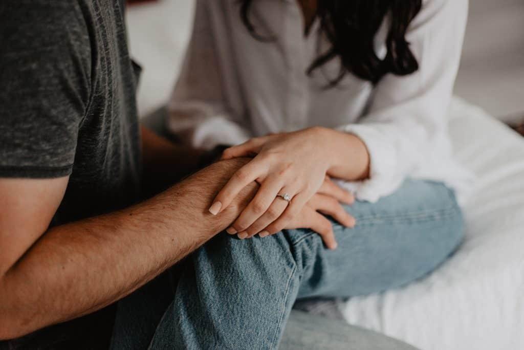 Mulher segurando a mão de homem com ambos sentados em uma cama.