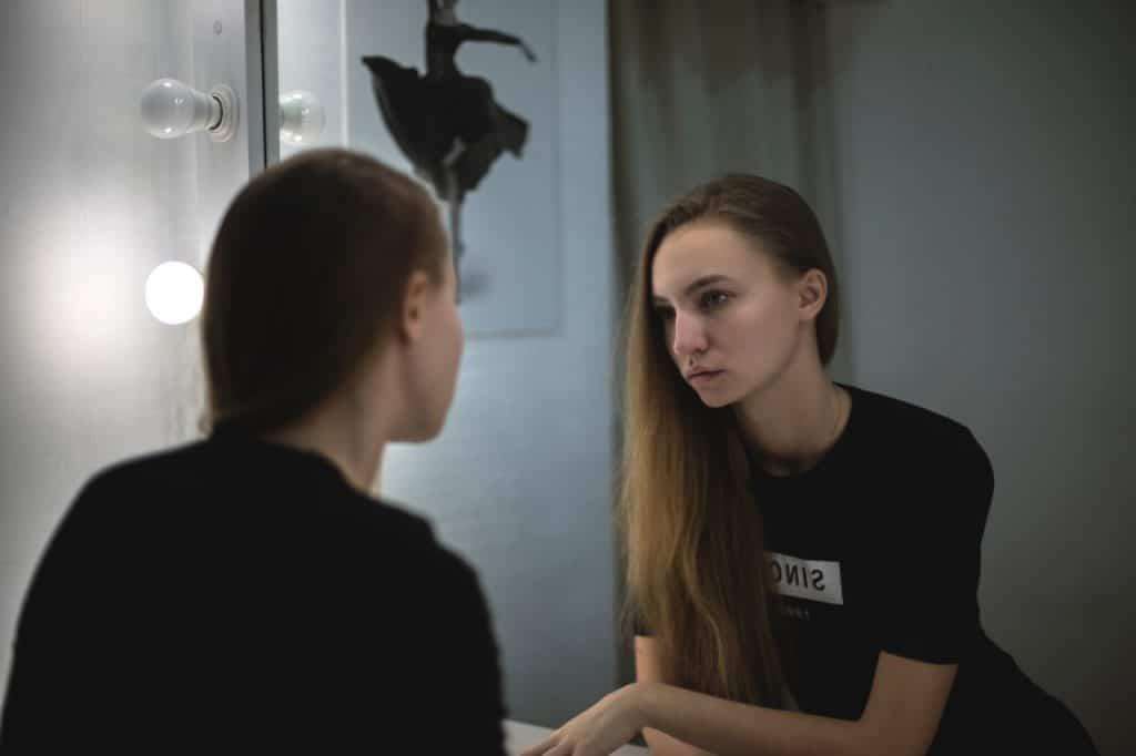 Menina jovem de roupa preta olha seu reflexo no espelho com aspecto triste.