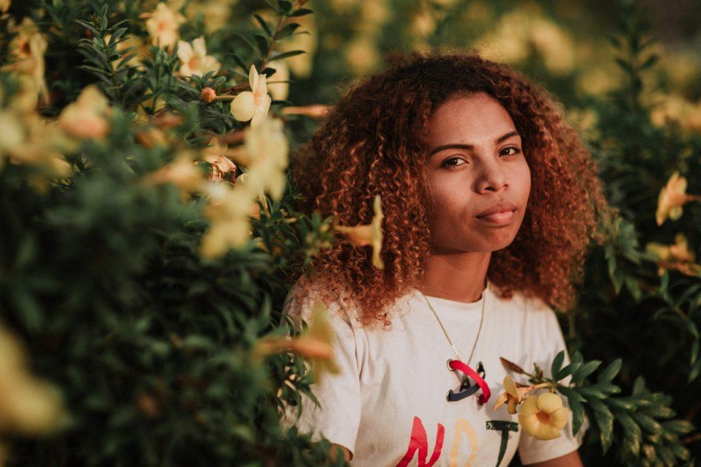 Retrato de mulher de cabelos cacheados em meio a flores amarelas.