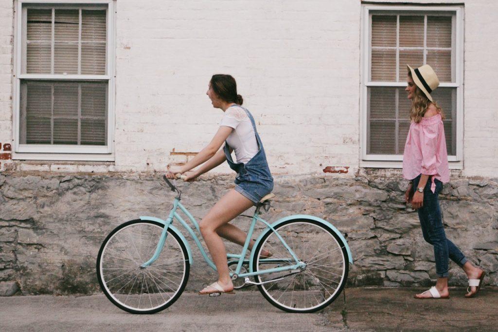Mulher andando de bicicleta e outra mulher atrás, seguindo a pé.