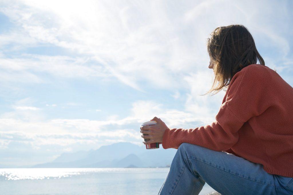 Mulher sentada na praia, com roupas de frio, segurando um copo de café e olhando para o horizonte.