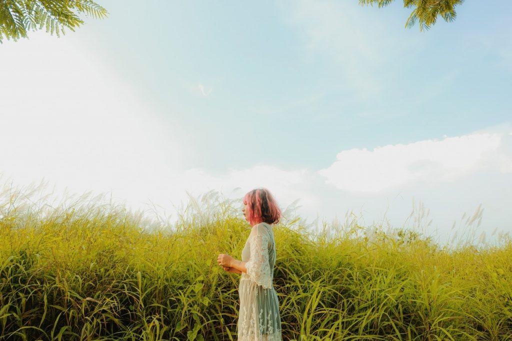 Mulher em pé de perfil com mato alto ao fundo e céu azul