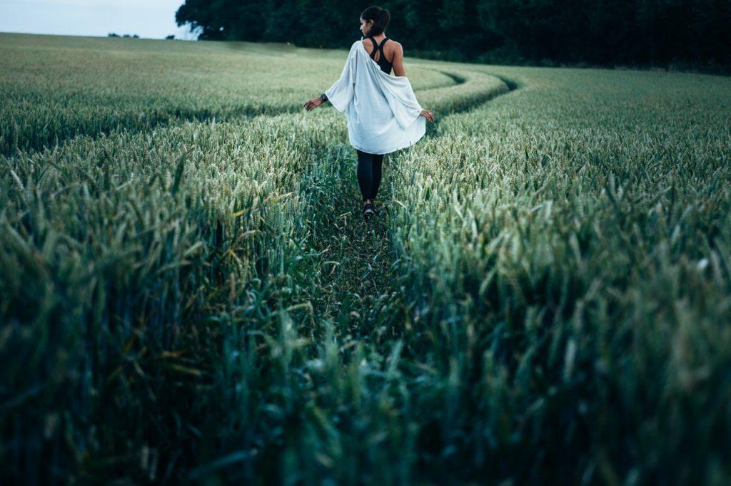 Mulher de costas caminhando em campo verde