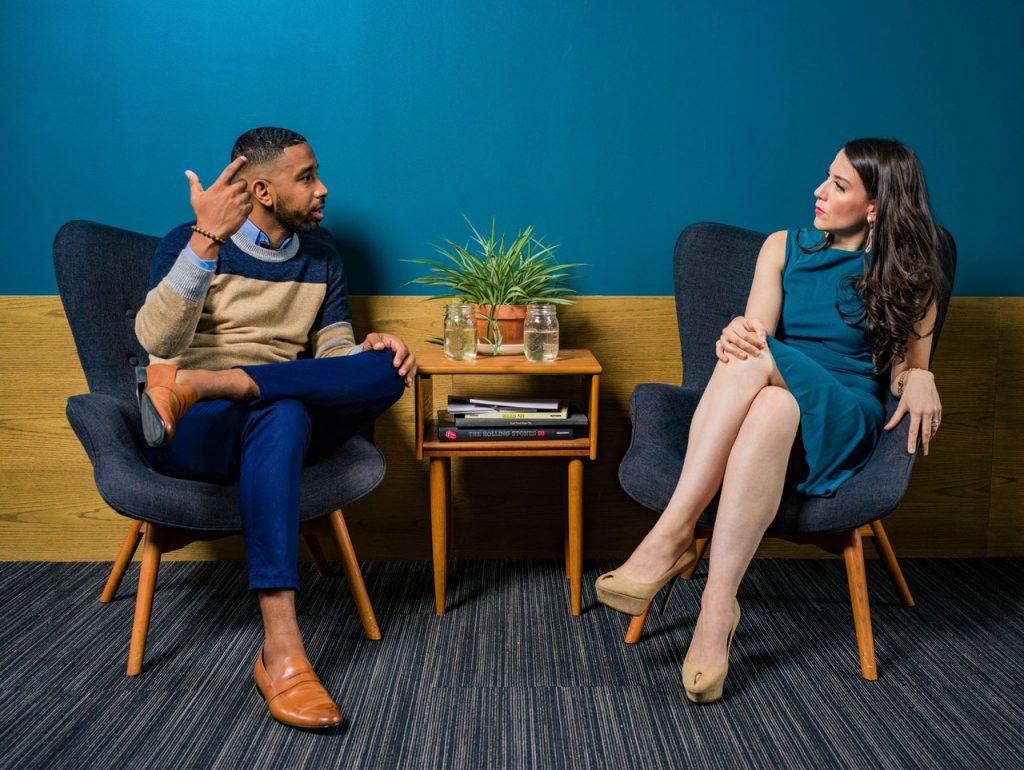 Uma mulher e um homem estão sentados em poltronas, um ao lado do outro, aparentemente discutindo.