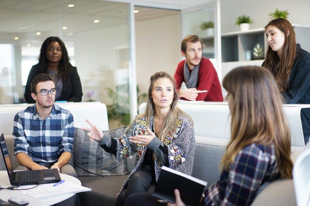 Grupo de pessoas em ambiente corporativo, conversando de maneira saudável.