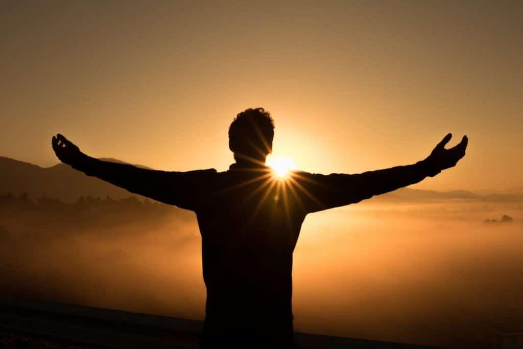 Silhueta de homem de costas com braços abertos e sol refletindo ao fundo