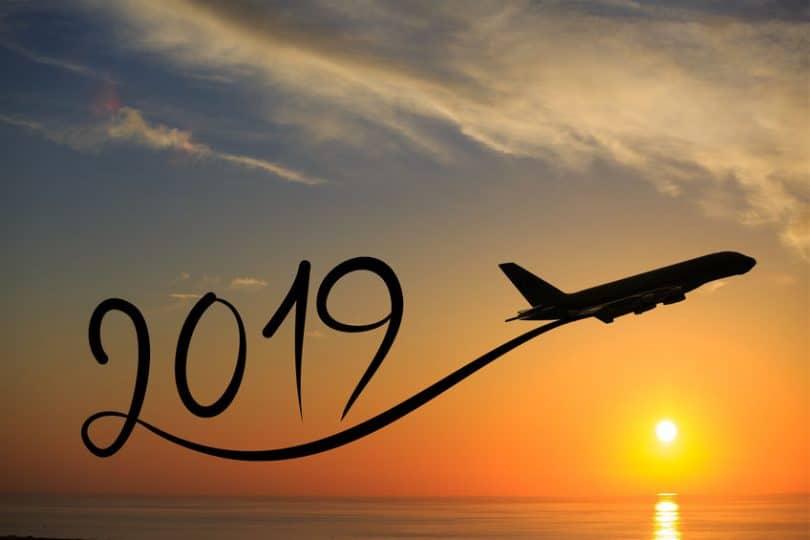Imagem manipulada de avião voando no céu, sobre o mar e durante o nascer do sol. Ele deixa uma especie de rastro que forma os números 2019..
