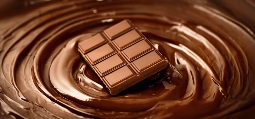 Barra de chocolate sobre o fundo de um mousse de chocolate derretido.